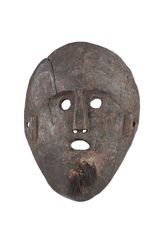 Masque de crmonie shamanique Visage aux formes pures, s'inscrivant dans un espace ovale. Bois dur, ancienne patine d'usage brune brillante par endroits. Npal. H. : 32 cm.