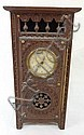 FRENCH CLOCK IN A SIGNED, CARVED WOODEN CASE W/TURNED SPINDLES; 10 5/8 IN H, 5 3/8 IN W