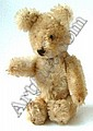 A small Schuco 'Yes/No' bear with blond plush, stitched nose and glass eyes, tail covering missing, 13cm.