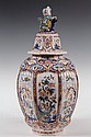 DUTCH DELFT POTTERY - Polychrome oviform covered jar, 19th Century, red FL 5/1 mark, ribbed sides in the Chinese style with panels of t