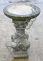 A reconstituted stone bird bath with a circular
