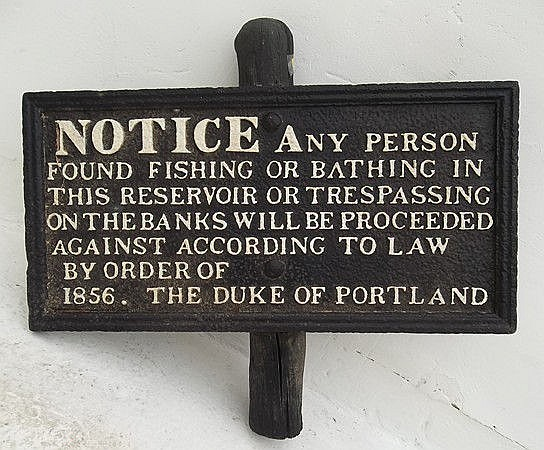 A black cast iron sign picked out in white