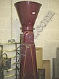 A maroon coloured tall grinding machine