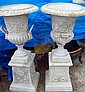 A pair of white cast iron urns on bases after