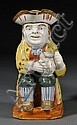 Pratt-type Staffordshire Toby Jug, England, c. 1800, typical underglaze enamels to a well-modeled figure seated and holding a frothi...